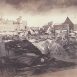 Rubble of buildings destroyed by fire, showing stack of corrugated iron and other rubble, sign still standing reads: Bennett's Pharmacy / Temporary Premises / next / Romney Studios. Man standing among rubble in background.