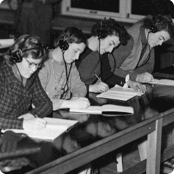 four students with headphones and notebooks seated in a row
