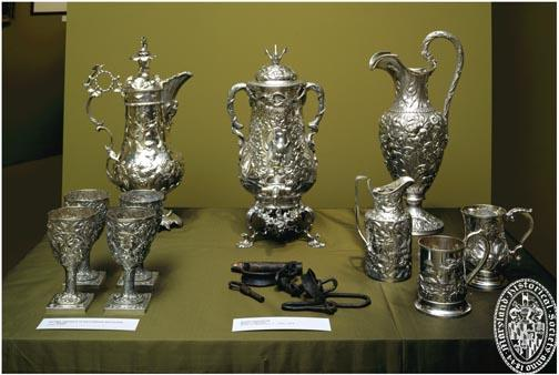 Display case containing fine silverware and slave shackles