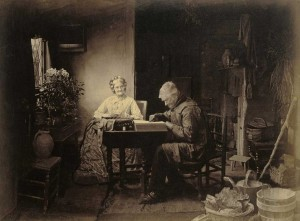 Elderly couple sitting at a table. She is darning socks; he is reading.